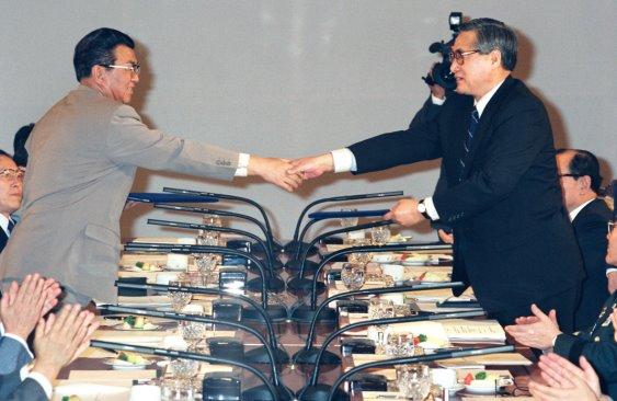 es deux leaders coréens se serrent la main par-dessus une table longue (© As