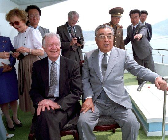 immy Carter et Kim Il Sung assis ensemble, des personnes debout à l'arrièr