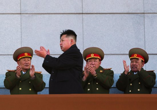 im Jong-un, debout devant trois hommes en uniforme assis derrière lui, en t